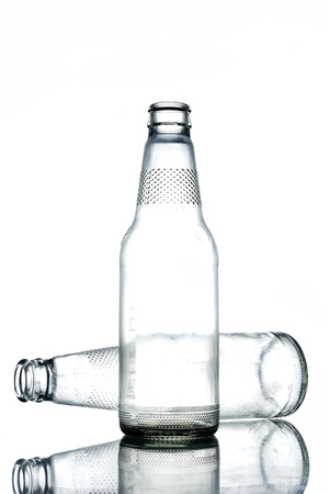 Empty colorless glass bottles on a white background.