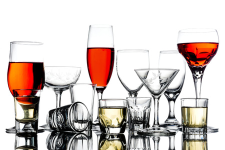 Collage of empty glasses with alcohol on white background. Stock Photo