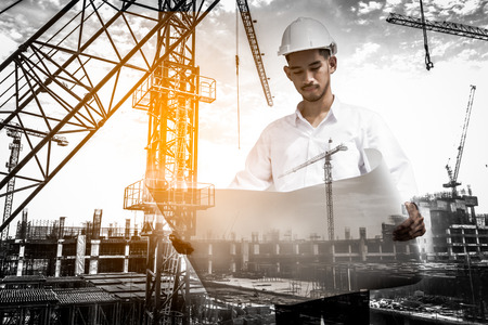 Double exposure of civil engineer holding blueprint with construction site. Stockfoto