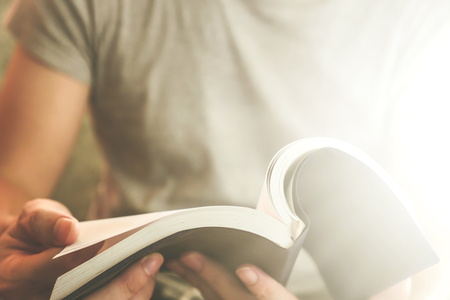 Close up of male hands holding a book to read, Flare from the sunlight