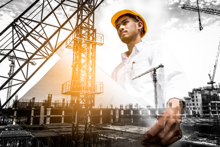 Double exposure of civil engineer holding blueprint with construction site. Archivio Fotografico