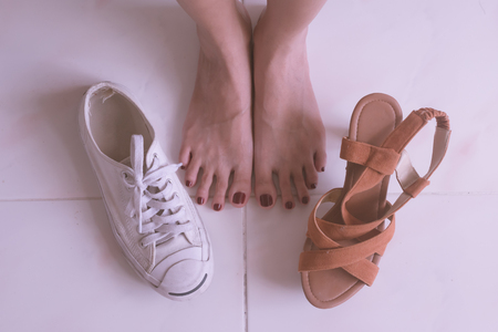 Close up of female feet with high heels shoes and casual sports shoes. Stok Fotoğraf