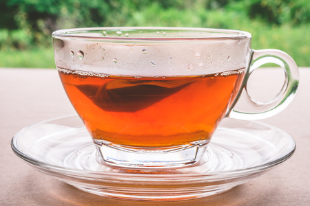 close up: A cup of tea on the wooden table, tea bag in glass, nature background.