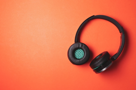 Modern headphones on a orange background. Free space for text 版權商用圖片