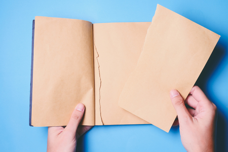 wrest: Top view of hands tear paper in notebook on blue background. Stock Photo