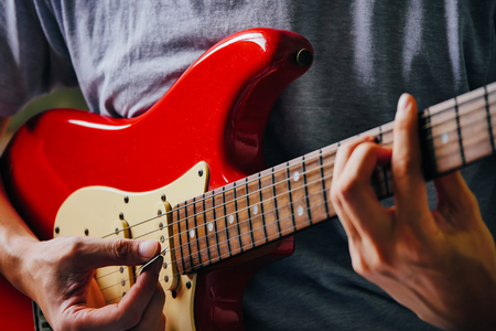 Close up of male hands playing electric guitar. Selective focus