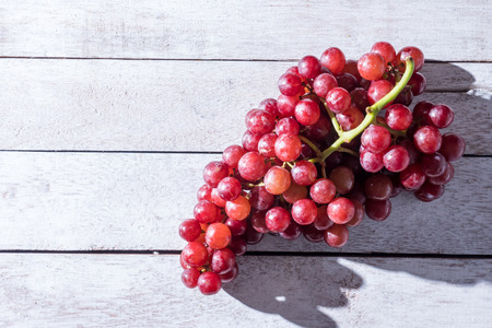 Top view of Red grapes on the wooden table. Free space for text