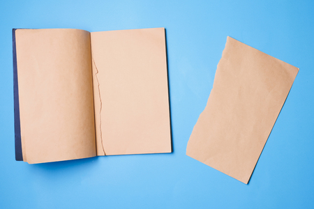 Blank notebook with a piece of note paper on blue background. Фото со стока
