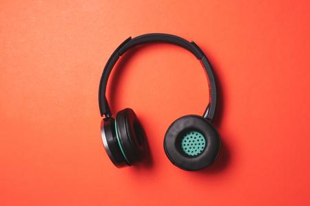 オレンジ色の背景上にモダンなヘッドフォン。 写真素材