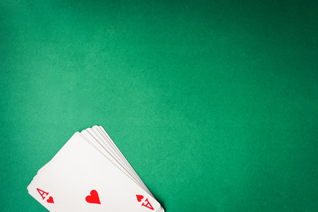 Playing cards on green background. Free space for text Reklamní fotografie