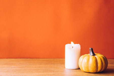 Pumpkin With Candlelight On An Orange Color Background. Free Space For Text  Photo