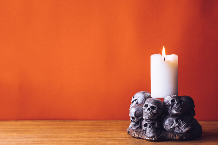Skulls with a candle burning on an orange color background. Free space for text