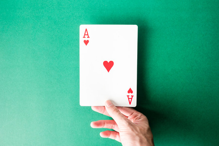 Hand holding a playing card on green background.