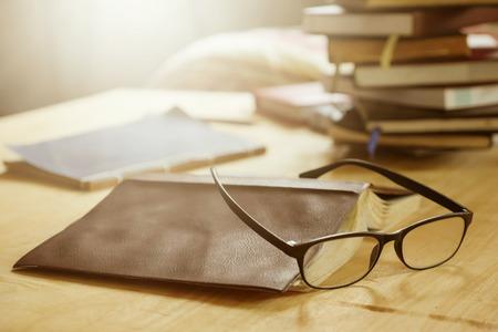 木製のテーブルの上に本を持つ眼鏡、ソフトフォーカス、フレアサンライト、ヴィンテージトーン。 写真素材