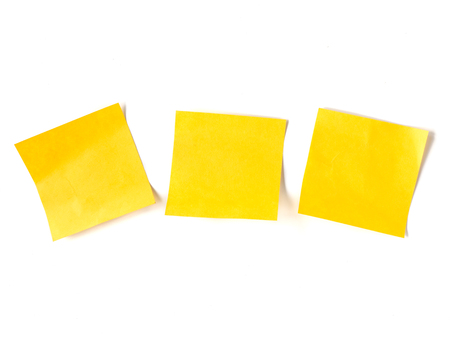 Yellow stick notes paper on white background. Imagens