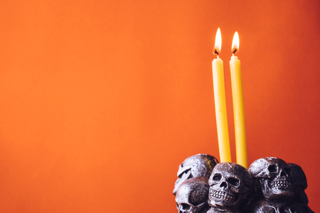 Skulls with candle burning on an orange color background. Free space for text Stock Photo