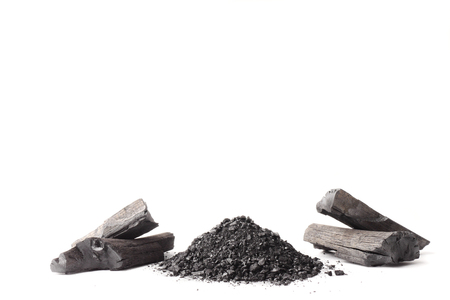 Charcoal and powder (activated carbon) on white background. Free space for text