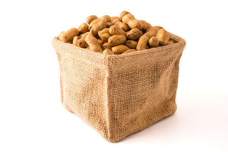Peanuts in burlap bag on white background. 版權商用圖片