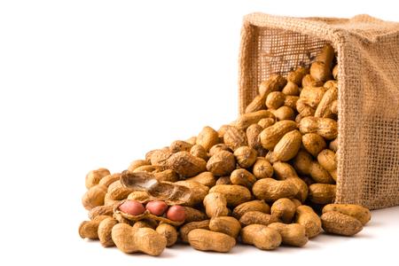 Peanuts in burlap bag on white background. Standard-Bild