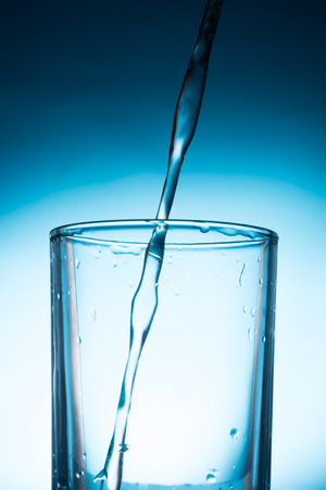Pouring water into glass on blue background.