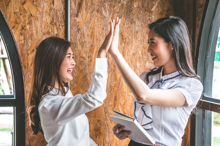 Successful business people giving high five together, finishing up a meeting.