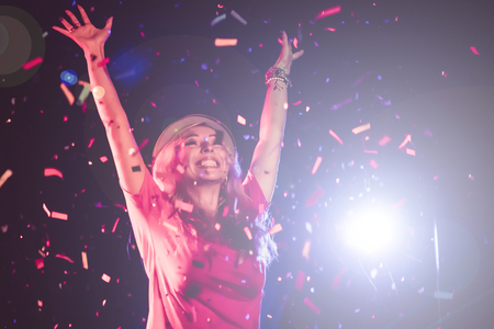 Happy woman dancing under confetti at a party