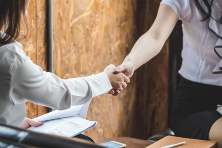 Successful business people shaking hands, finishing up a meeting. Фото со стока