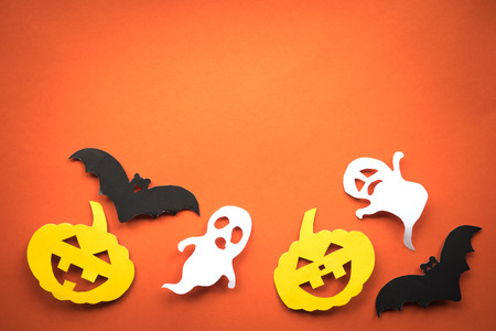 Halloween holiday background with pumpkins, ghosts and bats cut paper on orange background. Free space for text. Banco de Imagens