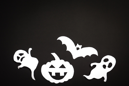 Halloween holiday background with pumpkin, ghosts and bat cut paper on black background. Free space for text.