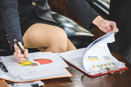 Close up of Businesswoman analyzing investment charts on the desk. Stock Photo