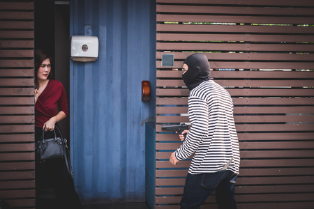 Thief is looking at an asian woman who is in a toilet alone because he want to steal her bag.