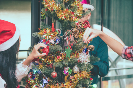 Group of friends decorating Christmas tree before Chrismas party. Stock Photo