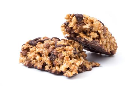 Barrette di cereali al cioccolato con grano integrale e cioccolato su uno sfondo bianco. Archivio Fotografico - 89904939
