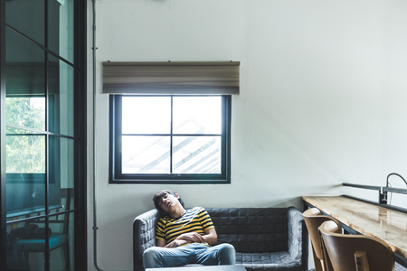 Asian young man sleeping on sofa. Male relaxing or napping on couch.