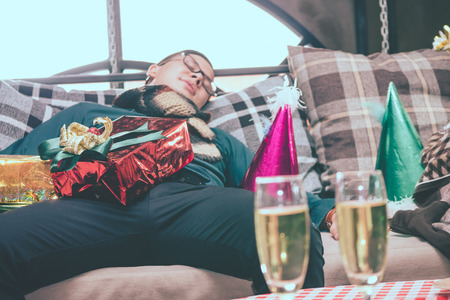 Sleeping man on a sofa after Christmas party. Stock Photo