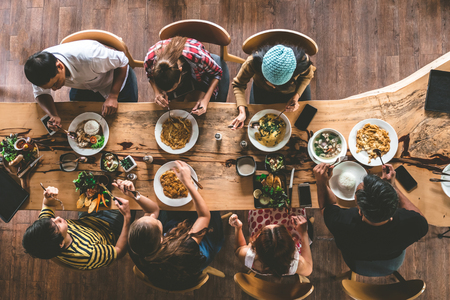Group of happy friends having nice food and drinks, enjoying the party and communication, Top view of Family gathering together at home for eating dinner. 免版税图像