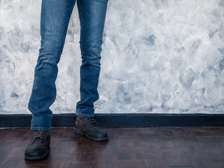 Close up of Mans legs in jeans and boots on wooden floor. Free space for text