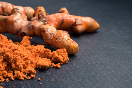 Turmeric roots with turmeric powder on black background.