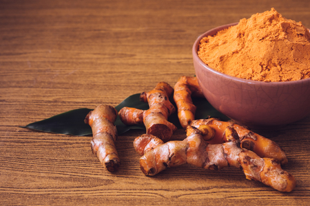 89728388-turmeric-roots-with-turmeric-powder-on-wooden-background-.jpg?ver=6