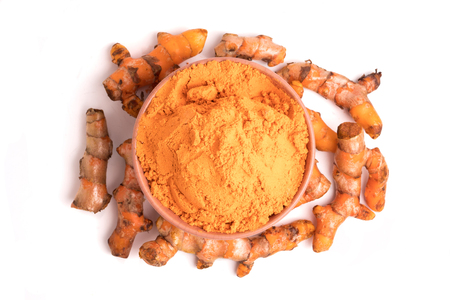 Turmeric roots with turmeric powder on white background.