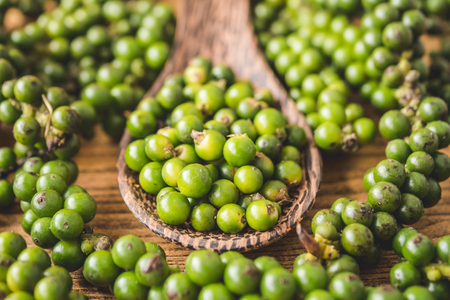 Green peppercorns on wooden background.