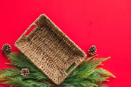 Empty basket with christmas tree branches on red background. Free space for text Banco de Imagens