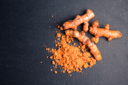 Turmeric roots with turmeric powder on black background. Stock Photo - 91006342