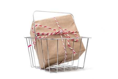 Gift package wrapped in brown paper in basket on white background. Stock Photo