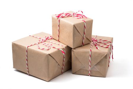Paquetes de regalo envueltos en papel marrón sobre fondo blanco. Foto de archivo - 90091074