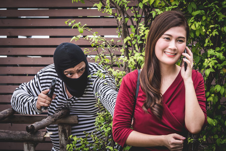 Thief is holding a gun and looking at asian woman, who is walking alone, and waiting for steal her bag. Stock Photo
