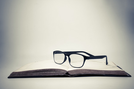 Eyeglasses on an open book with vintage background. Stock Photo