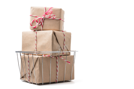 Gift packages wrapped in brown paper in basket on white background.