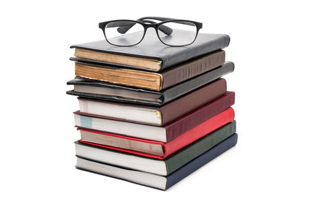 A stack of books with eyeglasses on a white background. Stockfoto