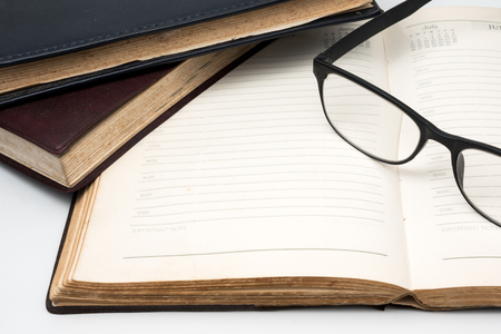 A stack of old books with notebook and eyeglasses on a white background.